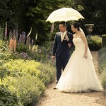 wedding couple under sun umbrella at Castle Ashby