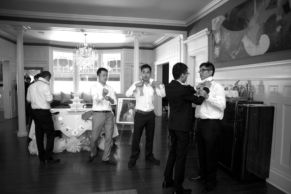 grooms men tying their bow ties