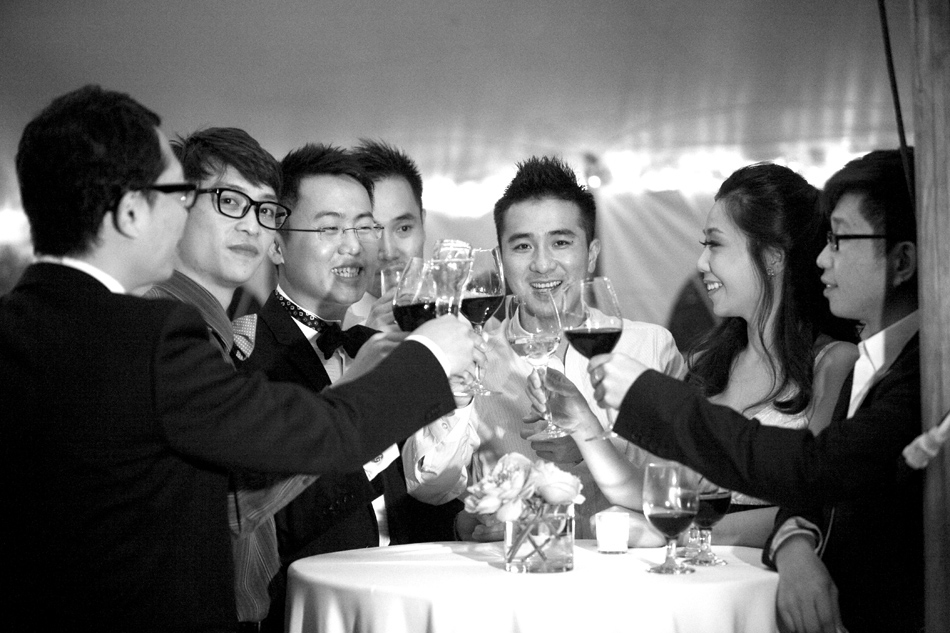 Black and whit photo of groom and his friend toasting