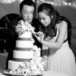Bride and Groom inspecting delicate icing work on their wedding cake