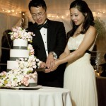 Photograph by Lisa Burrett of bride and groom cutting the cake