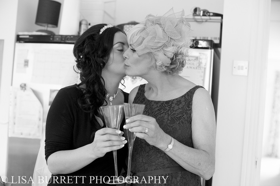 Mother of bride and bride kissing cheek