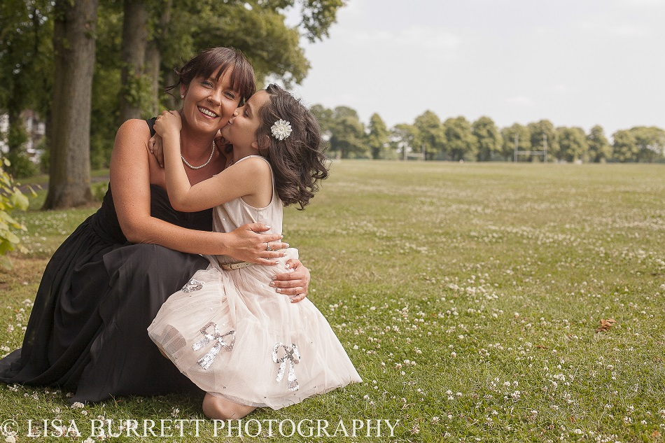 Daughter kissing mum in the park