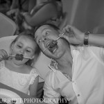 Black and white photo of dad and daughter eating from the chocolate fountain